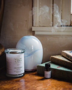 Essential oil aromatherapy blend with glass diffuser and scented soy candle by Willow & Birch Apothecary next to stack of antique books