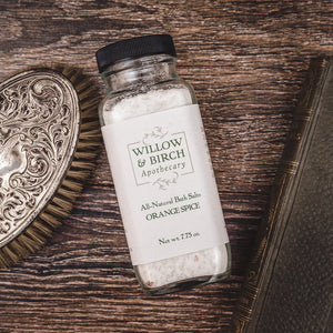 Orange Spice scented natural bath salts botanical epsom soak made with essential oils by Willow & Birch Apothecary with Victorian style hair brush and antique book