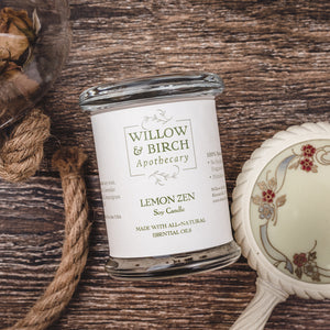 Lemon Zen natural scented soy candle made with essential oils from Willow & Birch Apothecary with antique vanity mirror and apothecary jar