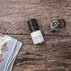 Orange Spice essential oil natural scent blend with orange, litsea cubeba, clove, and anise by Willow & Birch Apothecary with antique rings and vintage floral handkerchief