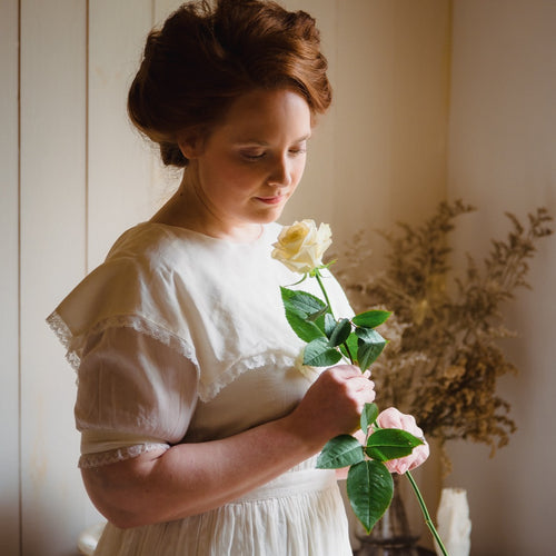 Woman in Victorian style dress holding a white rose