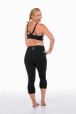 Back of woman wearing 3/4 black tights and pink activewear crop top