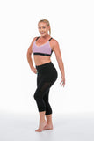 Woman wearing 3/4 black tights and pink activewear crop top front on