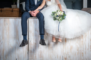 Bride and groom sitting down on a wall