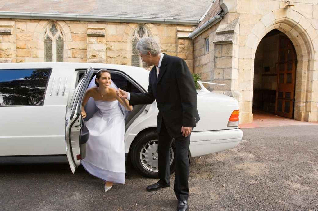Father helping bride out of limo
