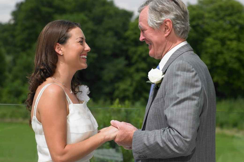 Bride and father smiling at each other