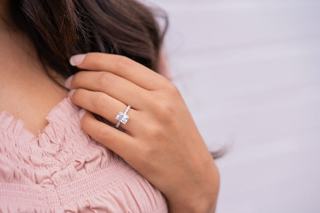 Woman's left hand touching her hair wearing The Alexandria on ring finger
