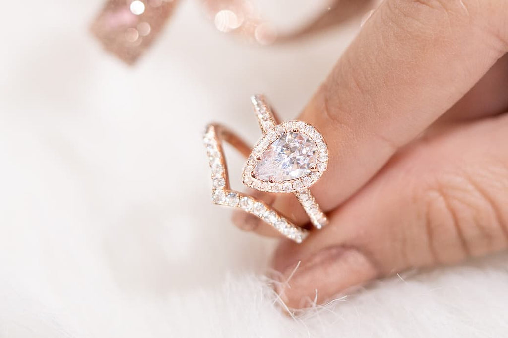 Woman's fingers holding The Bliss and The Zoey in rose gold