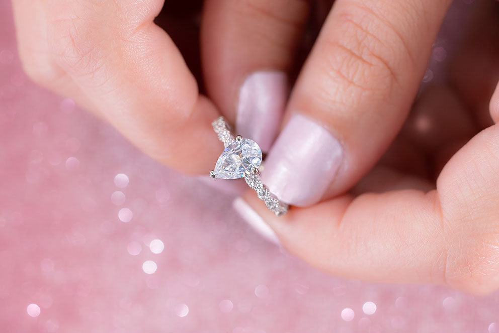 woman holding pear shaped engagement ring