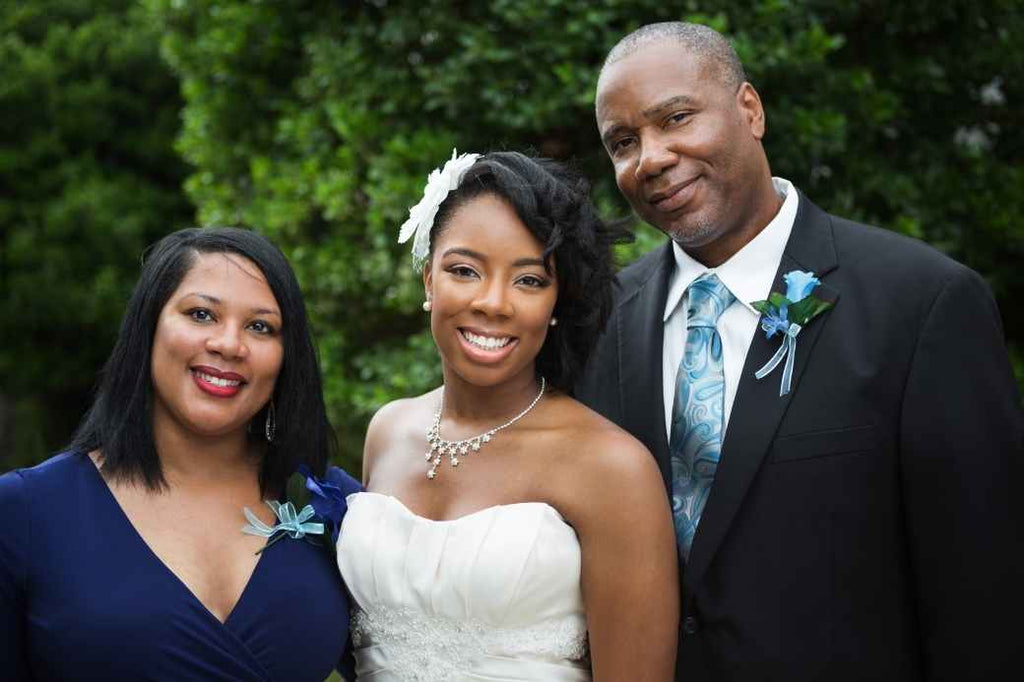 Bride posing with parents for photo