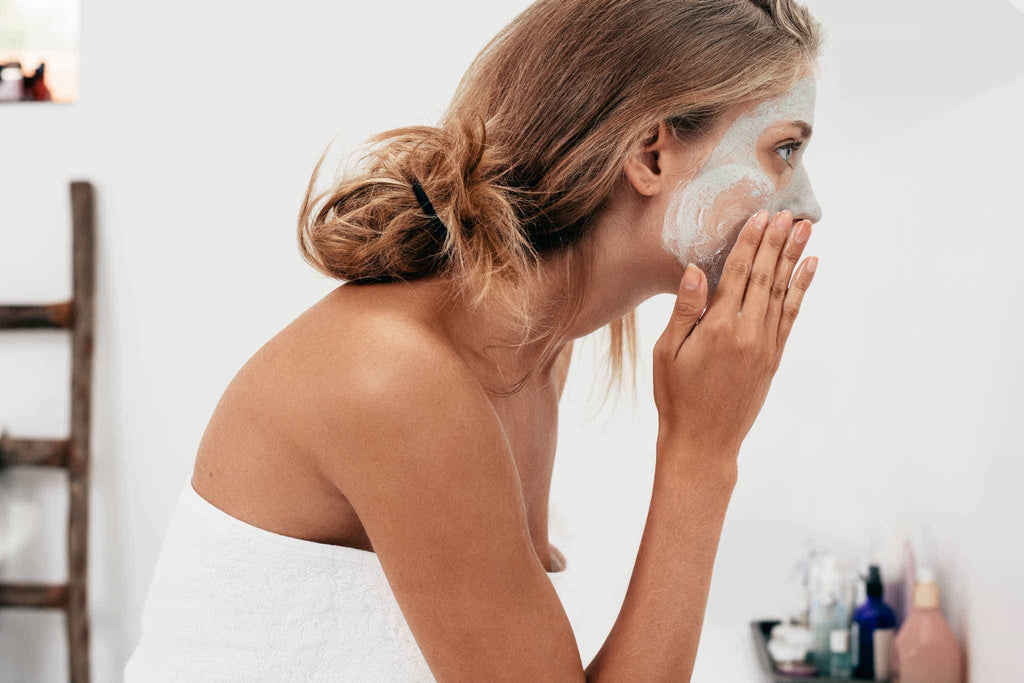 Woman applying a clay face mask
