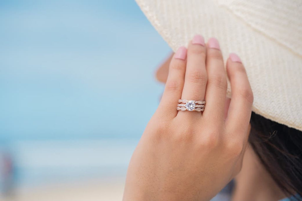 Woman's left hand touching hat at beach