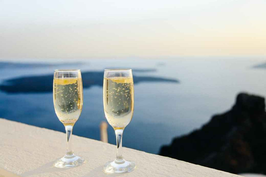 Two glasses of sparkling champagne with the ocean in the background
