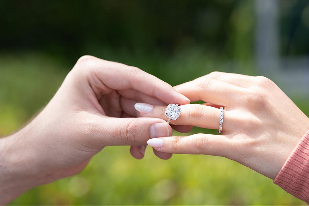 man placing a cushion cut engagement ring on a woman's finger