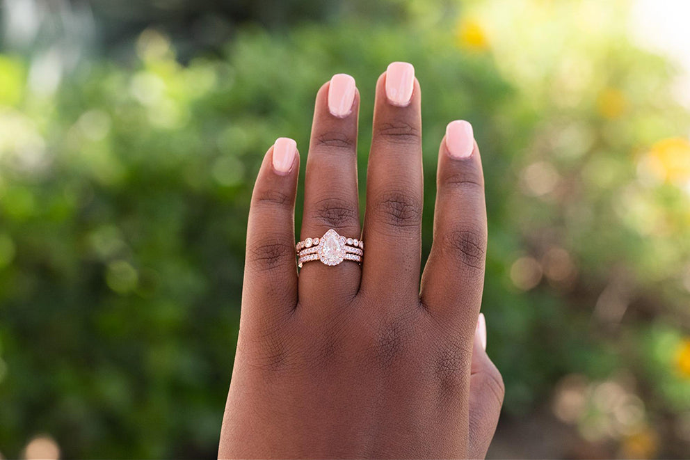 a close up of a womans hand wearing pear cut engagement ring