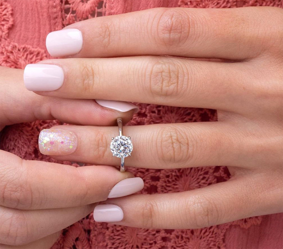 a close up of a woman trying on a silver engagement ring