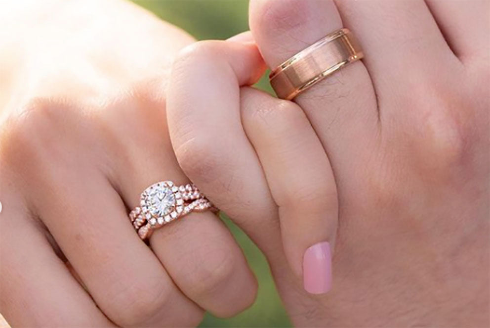 couple wearing wedding rings holding hands