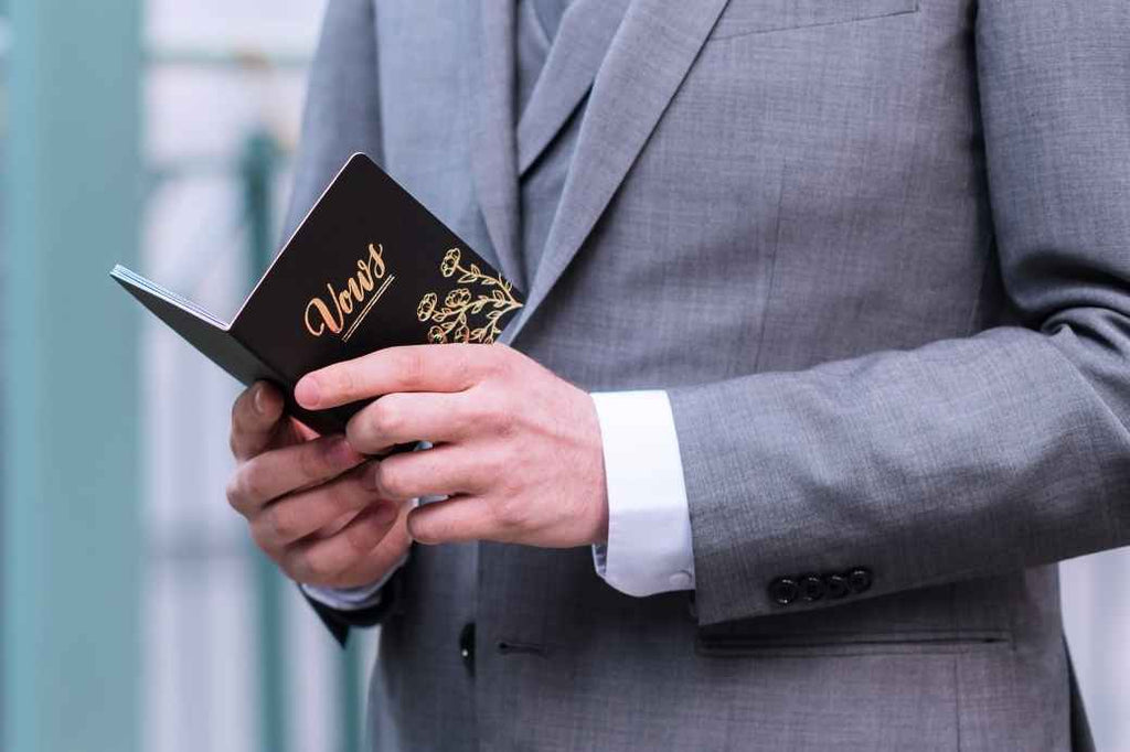 Groom holding wedding vows book