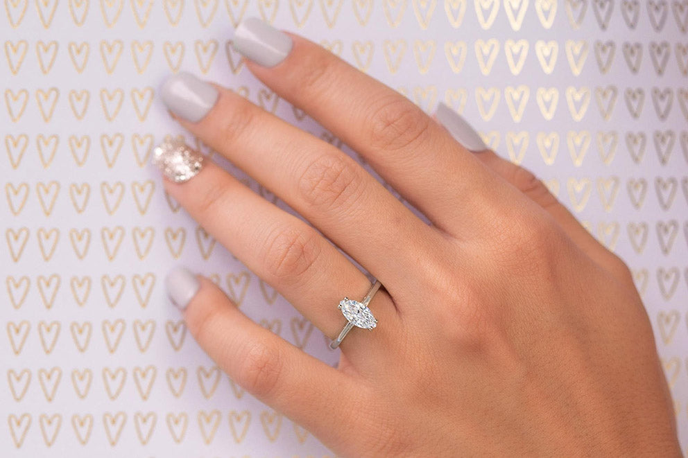 a close up of a womans hand wearing an elegant thin band engagement ring