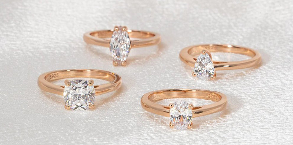 four dainty gold rings being displayed