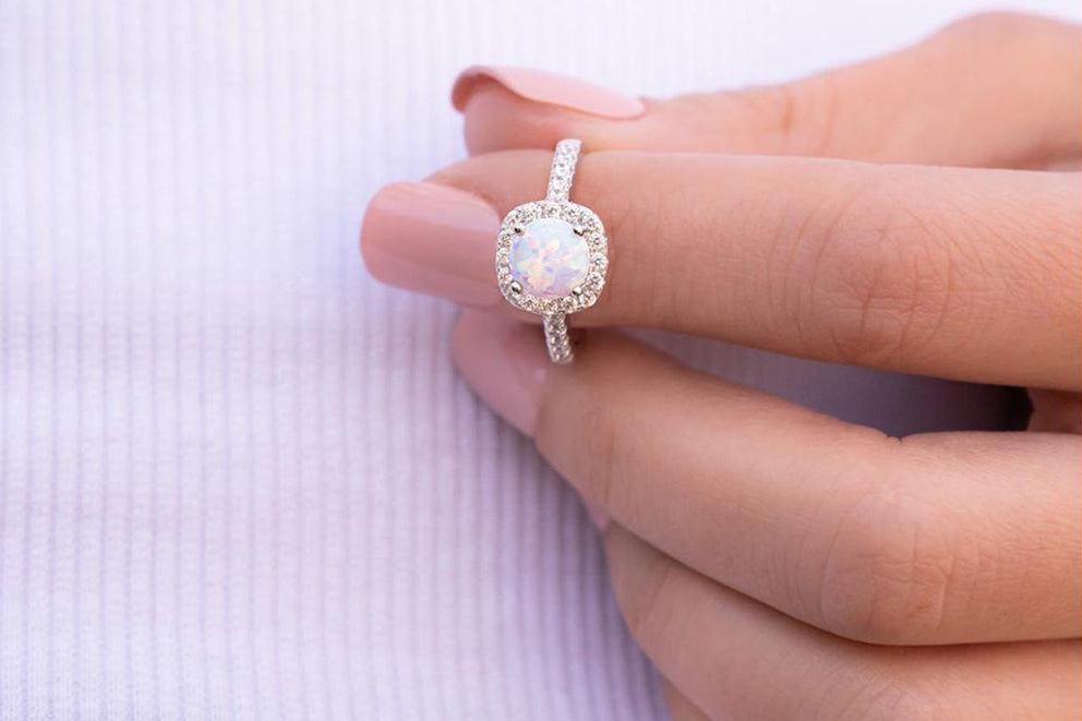 a woman holding the halo ring in opal