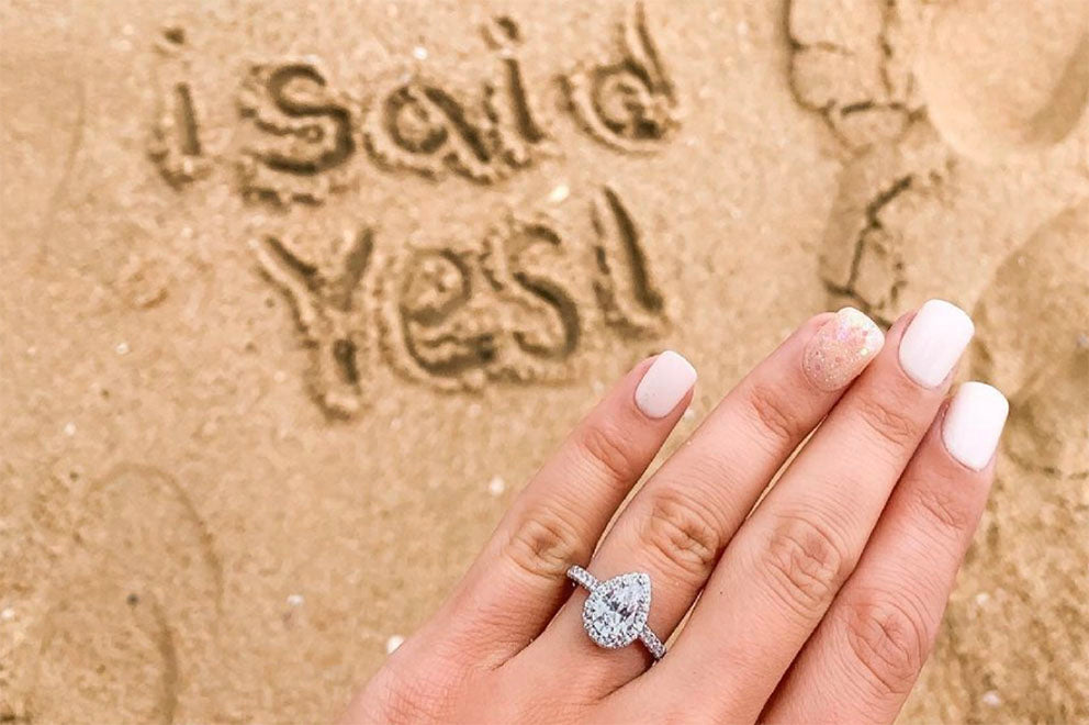 i said yes lettering in sand with engagement ring