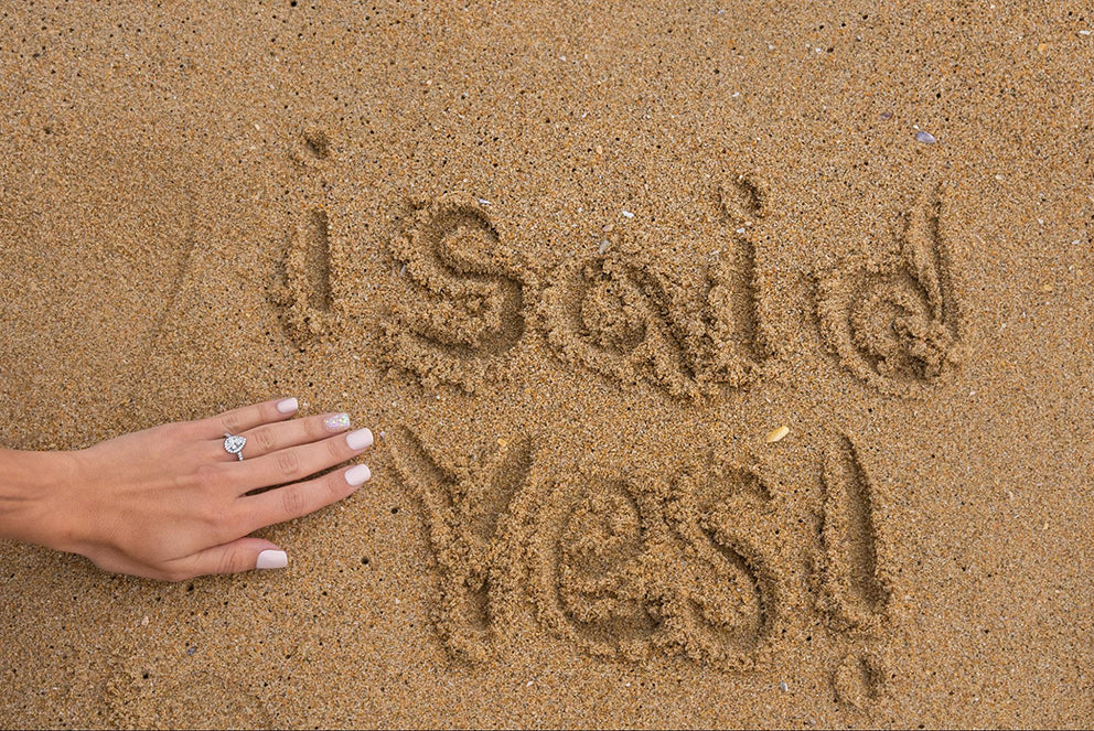 a woman showing off her engagement ring next to I said yes written in the sand