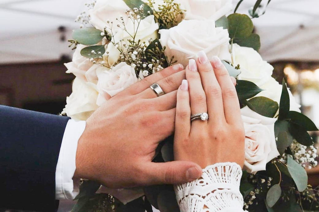 Married couple's hands in front of floral bouquet