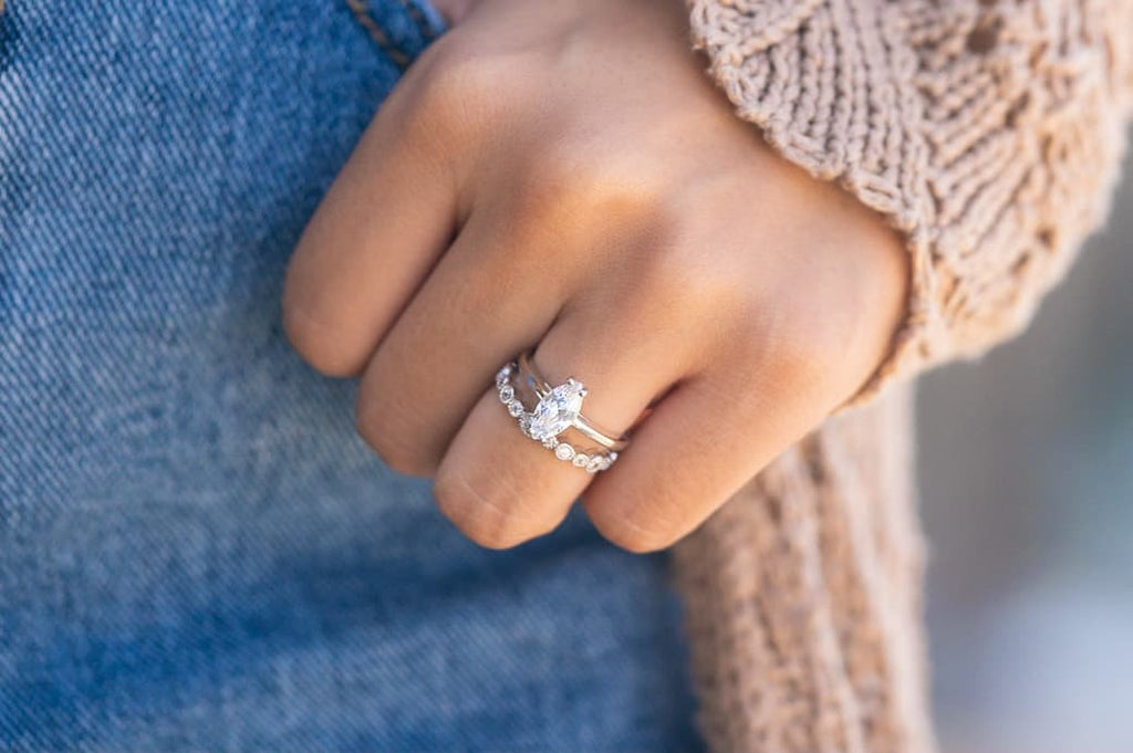 Woman's left hand wearing The Cambria and The Mia on ring finger