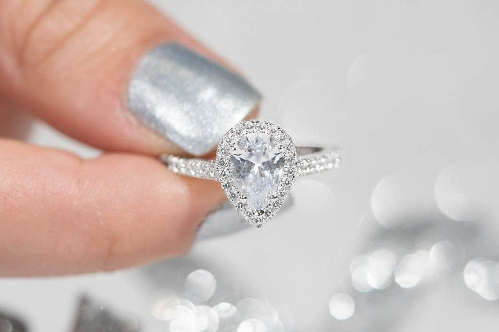 Woman's fingers holding The Bliss engagement ring