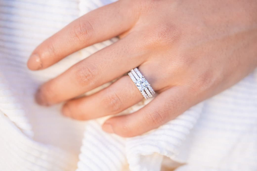 Woman's left hand wearing The Amore set and The Desire on ring finger