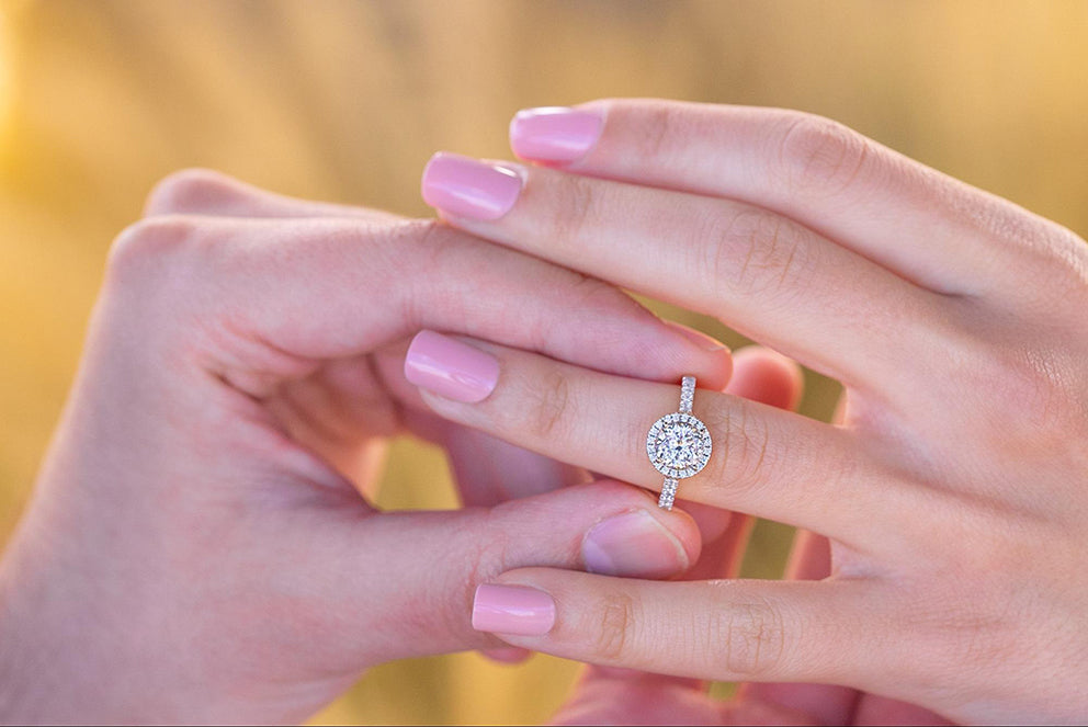 a person putting an engagement ring on a womans finger