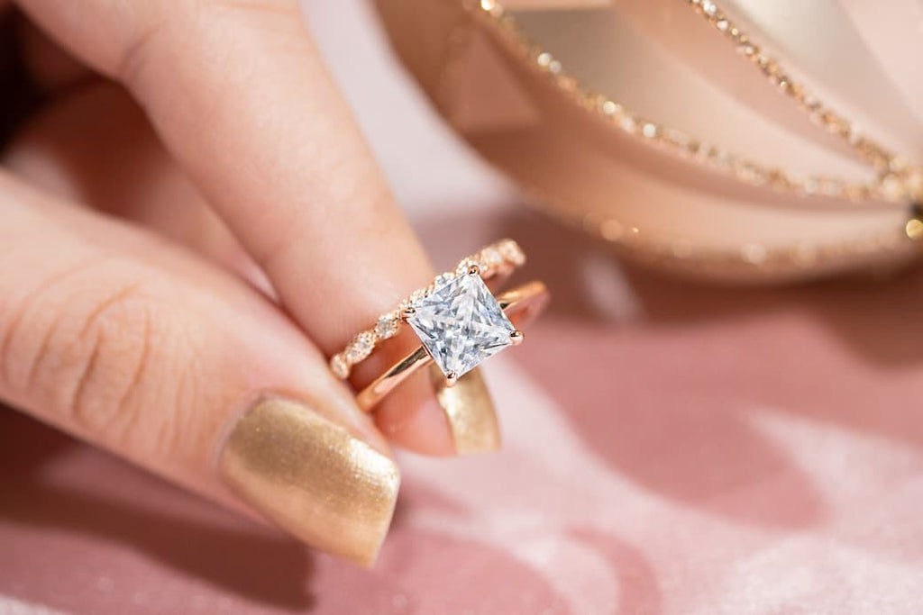 Woman's fingers holding The Olivia and The Forever in rose gold