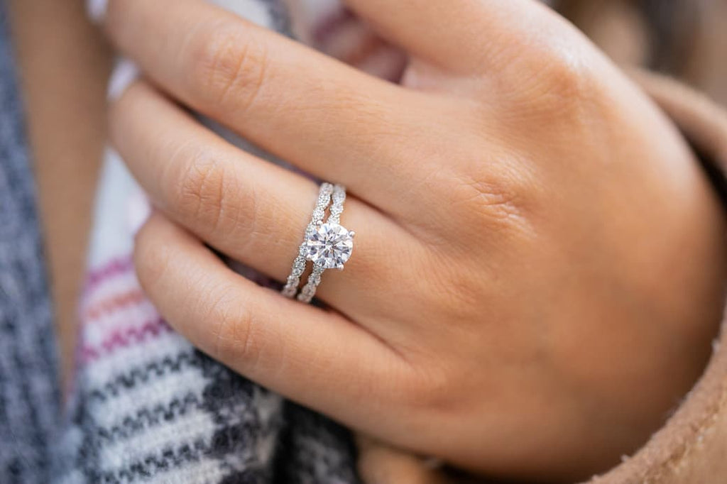 Woman's left hand wearing The Sofia and The Forever on ring finger