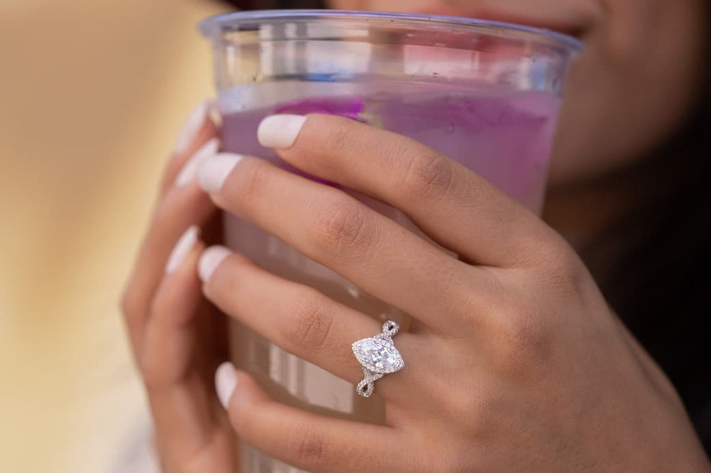 Woman's hands holding cup wearing The Victoria on left ring finger