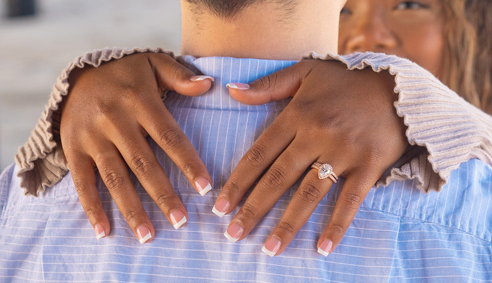 woman wearing a gold ring giving someone a hug