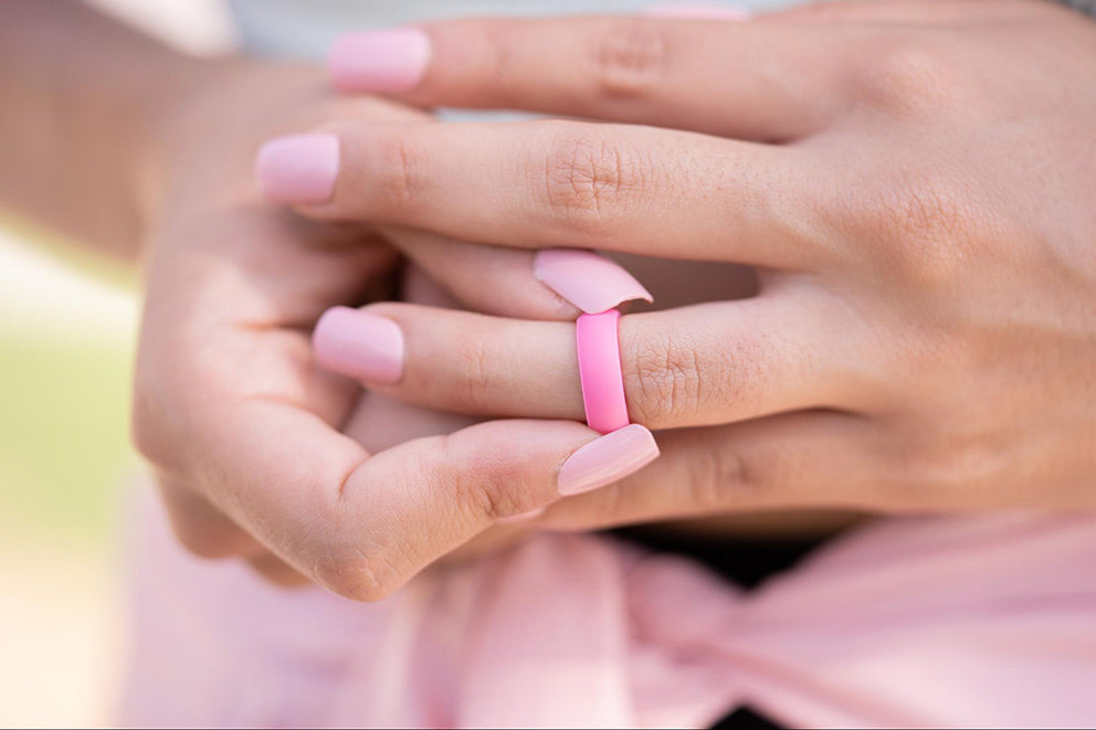 a woman putting on a pink silicone ring