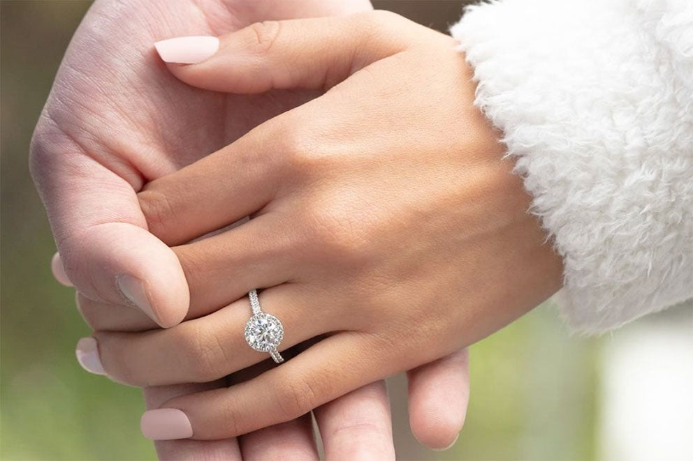 woman wearing engagement ring and holding partner's hand