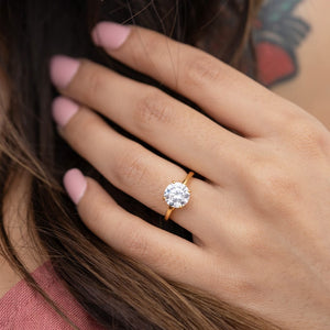 lady wearing the one and only gold round cut solitaire engagement ring