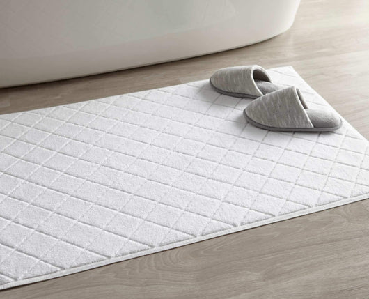 white diamond sculpted bath rug in bathroom with slippers