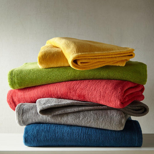 Messy stack of fuzzy blankets in various colors