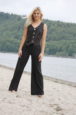 Model wearing black palazzo pants made with reclaimed textiles.