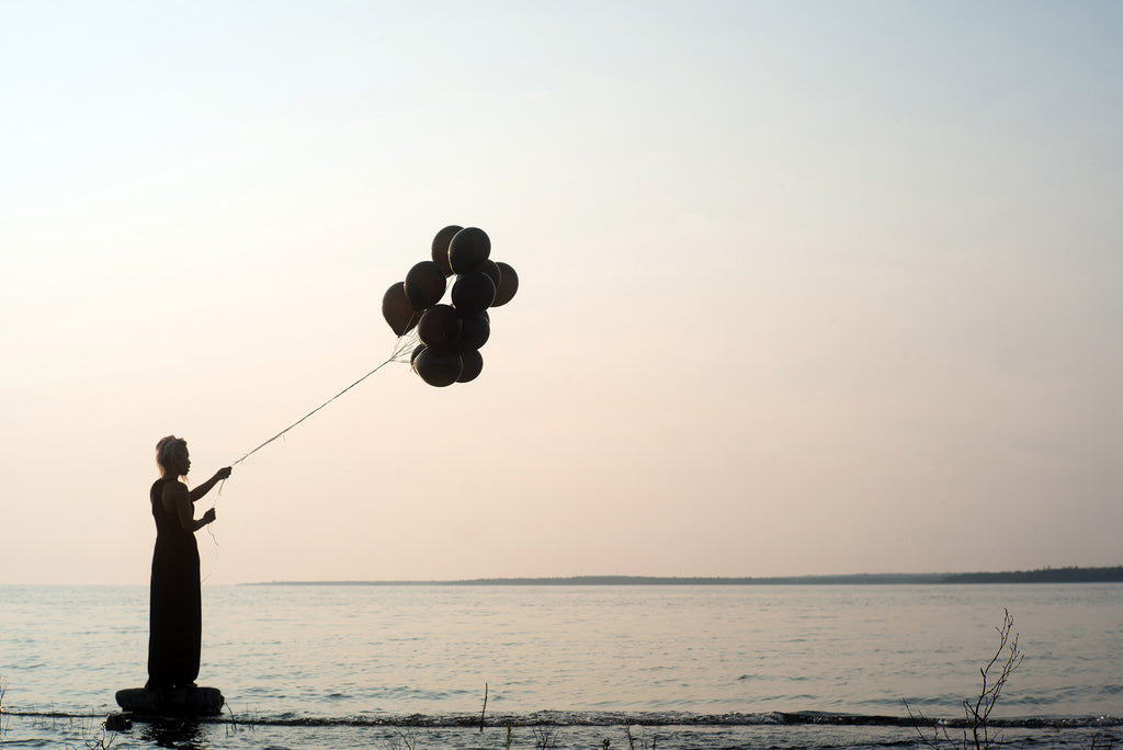 Woman with Balloons: Iolite Can Help You Let Go of What No Longer Serves You
