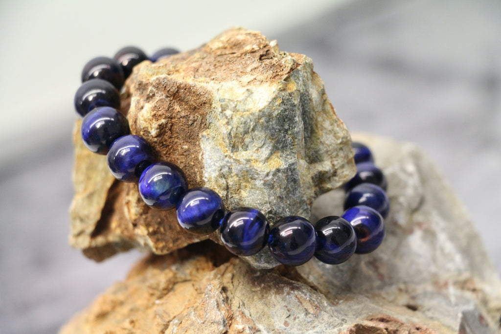 A blue tiger's eye bracelet displayed on a rock