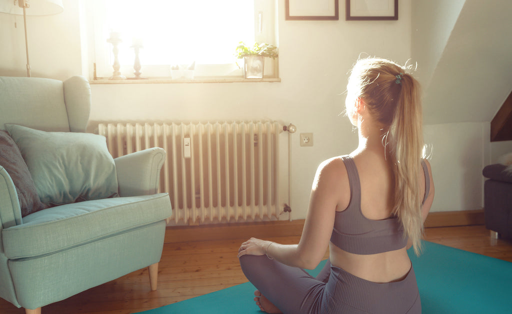 A woman meditating on a yoga mat in a bedroom