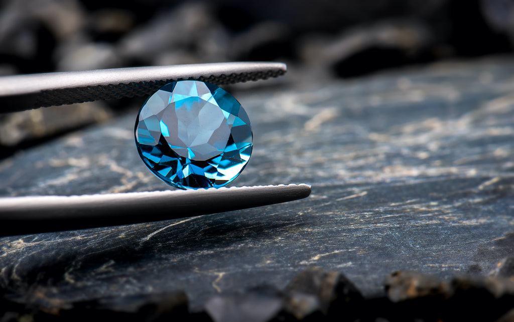 Tweezers hold a faceted blue topaz stone for high-end jewelry