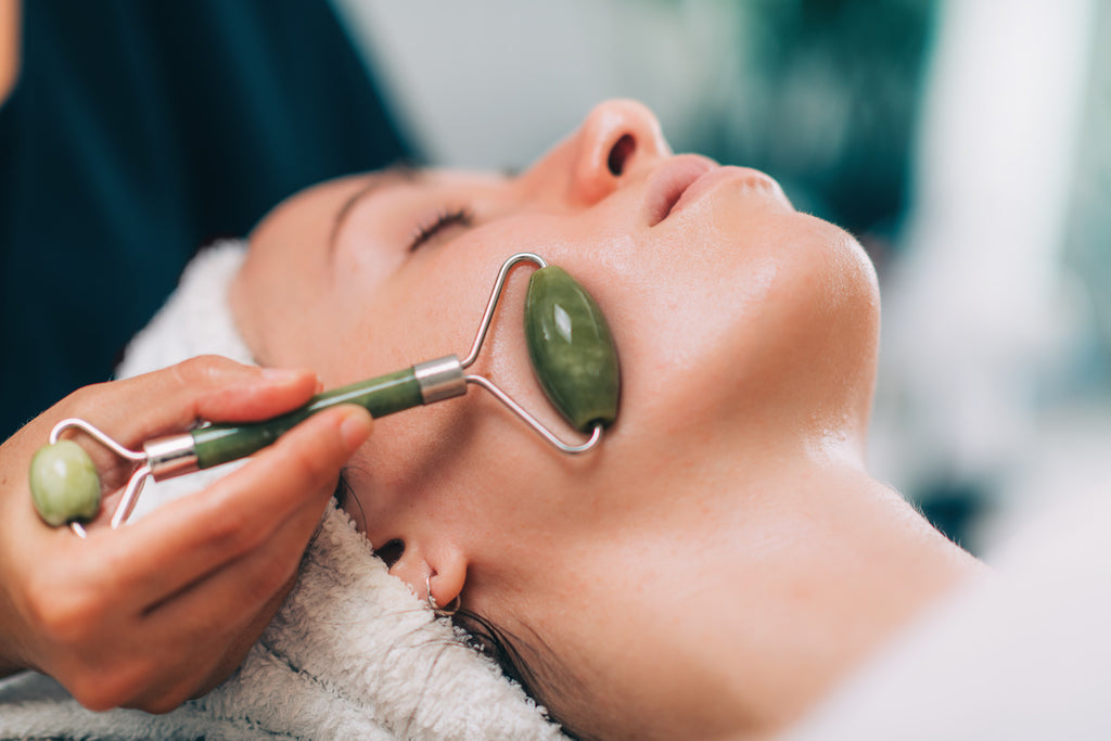 A cosmetologist uses a jade roller on a woman's face