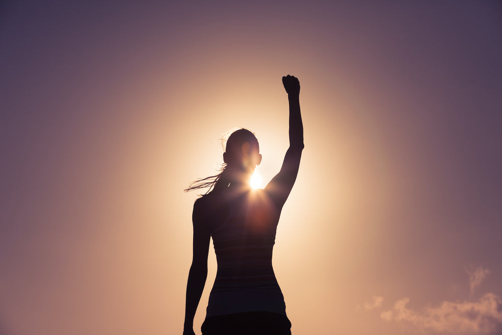Silhouette of a woman with her fist in the air