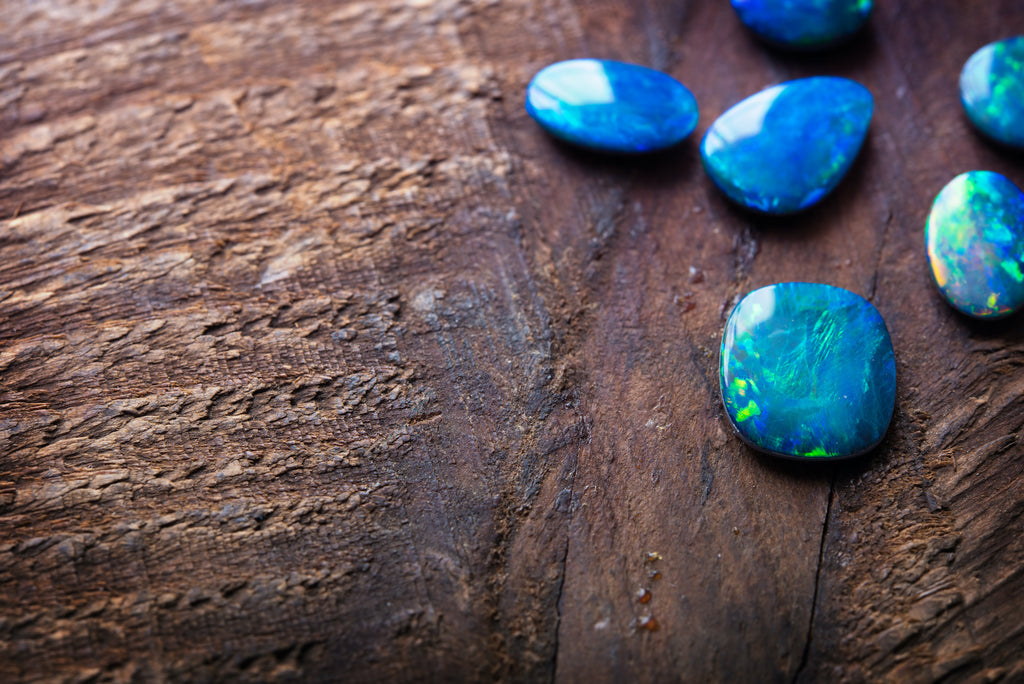 Blue opal stones laid out on a wood surface