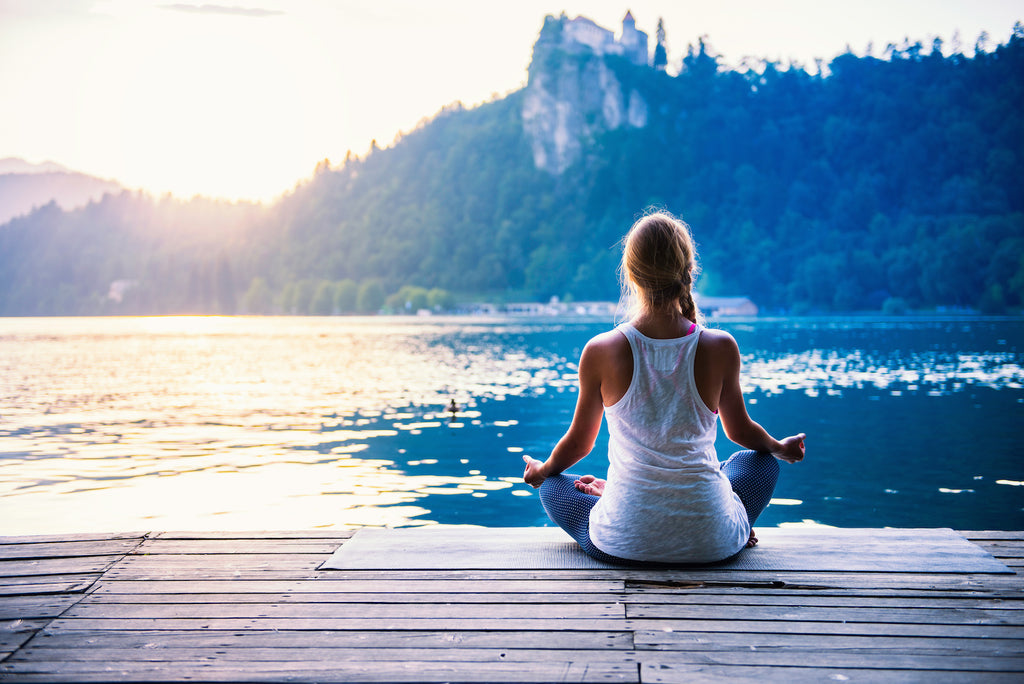 A woman meditates in front of a lake